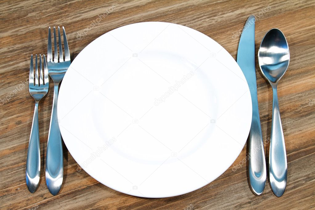 Modern silverware arranged in a place setting on a table — Stock Photo #7339748