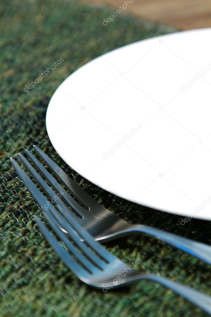 Modern silverware arranged in a place setting on a table  Stock Photo #7452010