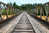 Old bridge over a brown river — Stock Photo