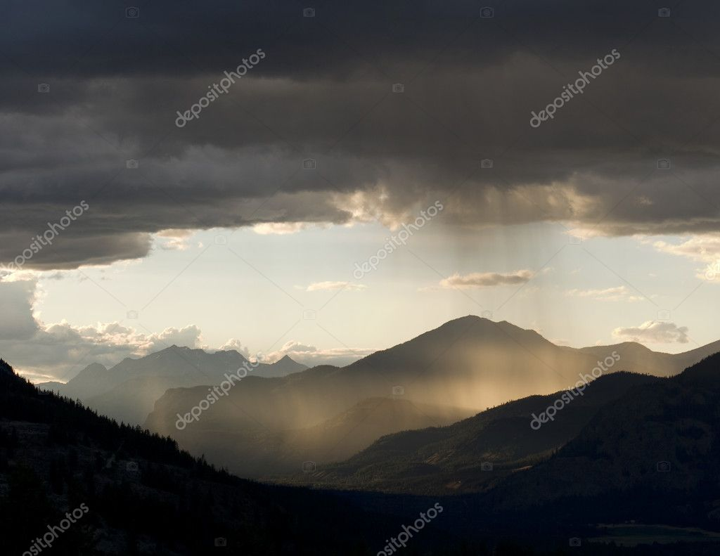 Light at sunset illuminates rain and storm clouds. The mist in the center is rain that is visible in the late day sunlight. — Stock Photo #7337828