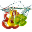 Red, yellow and green abstract pepper splashing in clear blue wa — Stockfoto #7366864