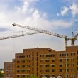 Three high heavy cranes on construction new big house — Foto Stock #7368019