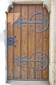 Crafty wooden door with metal ornament and metal handle — Stock Photo