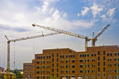 Three high heavy cranes on construction new big house — Стоковое фото