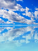 Scenery background - clouds in blue sky reflection in water — Stock Photo