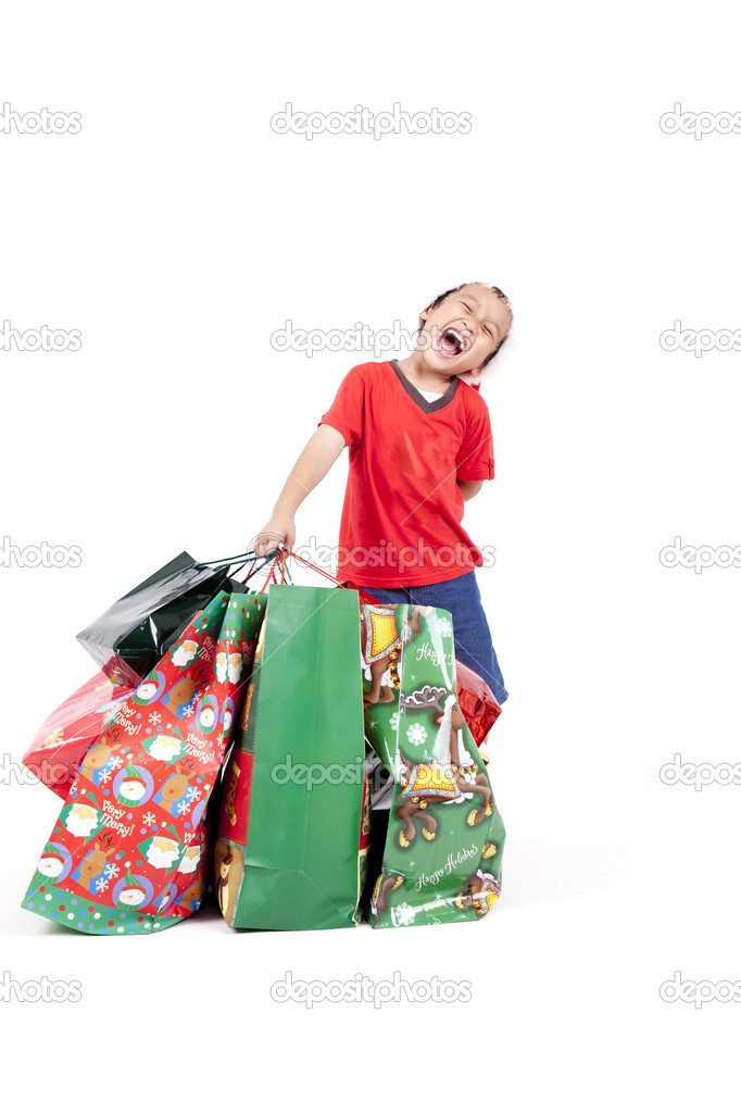 Happy boy carrying heavy shopping bag isolated on white — Stock Photo #7574286