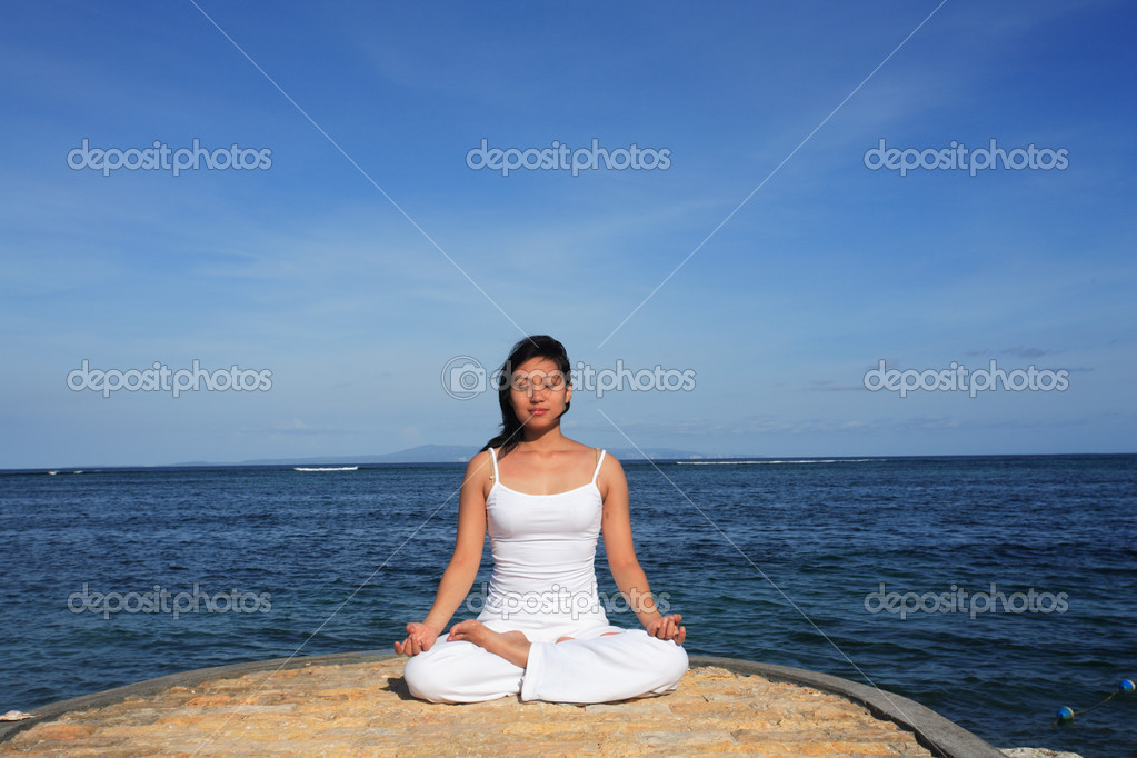 Woman meditating at beach — Stock Photo #7585276