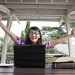 Stock Photo: Excited asiwomwith laptop and books