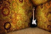 Guitare in a grunge textile room — Stock Photo