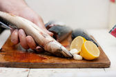 Fishermen cleaning and filleting a fresh caught fish — Stock Photo