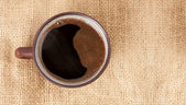 Cup of coffee standing on sackcloth — Stock Photo