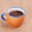 Cup of coffee standing on sackcloth - Stock Photo