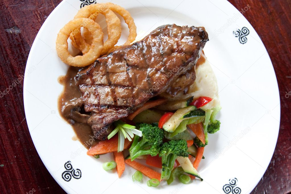 10 oz. New York Striploin Angus steak topped with Irish whiskey gravy, sautéed mushrooms and onion rings. Served with fresh vegetables and mashed potatoes. Goes — Stock Photo #7613081