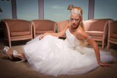 Young bride in white dress seated on the floor. — Stock Photo