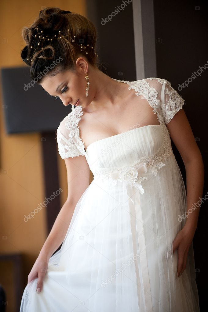 Beautiful brunette bride in white dress posing holding the dress and looking down. — Stock Photo #7407917