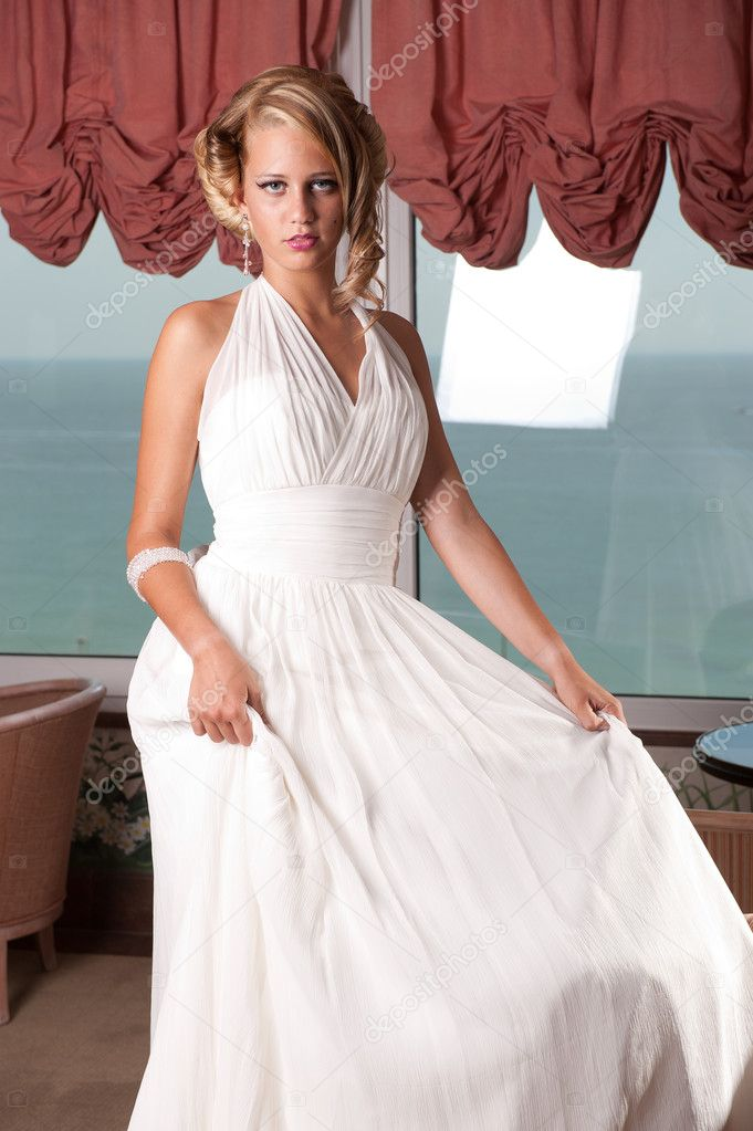 Beautiful blond young woman in wedding dress posing. Professionally done hair and makeup.  Stock Photo #7408412
