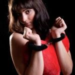 Sensual woman wearing handcuffs holding a heart shaped pillow — Stock Photo