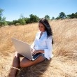 Stock Photo: Beautiful woman working on a laptop in the middle of a field