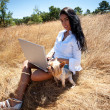 Beautiful woman working on a laptop in the middle of a field — Stock Photo