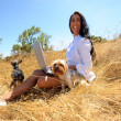 Beautiful woman working on a laptop in the middle of a field with dogs — Stock Photo