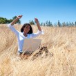 Stock Photo: Woman with a laptop on a field