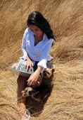 Όμορφη γυναίκα που εργάζεται σε ένα φορητό υπολογιστή στη μέση ενός χωραφιού με σκυλιά — Φωτογραφία Αρχείου