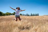 Woman jumping on straw field — Stock Photo