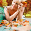 Women with autumn leafs - Photo
