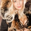 Beautiful blonde smile woman in a fur coat — Stockfoto