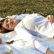Young woman stretching on bedspread in autumn park — Stock Photo
