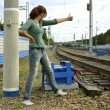 Young woman hitchhiking along a rail — Stock Photo
