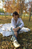 Young woman sitting on a blanket in autumn park — Stock Photo