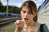 Young woman paints her lips on the railway — Stock Photo