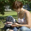 Stock Photo: Young woman sitting on grass with laptop
