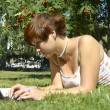 Stock Photo: Young woman lying on the grass in the park and chatting