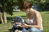 Young woman sitting on grass with laptop — Stock Photo