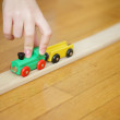 Child hand's playing with a wooden toy train — Stock Photo #7680246