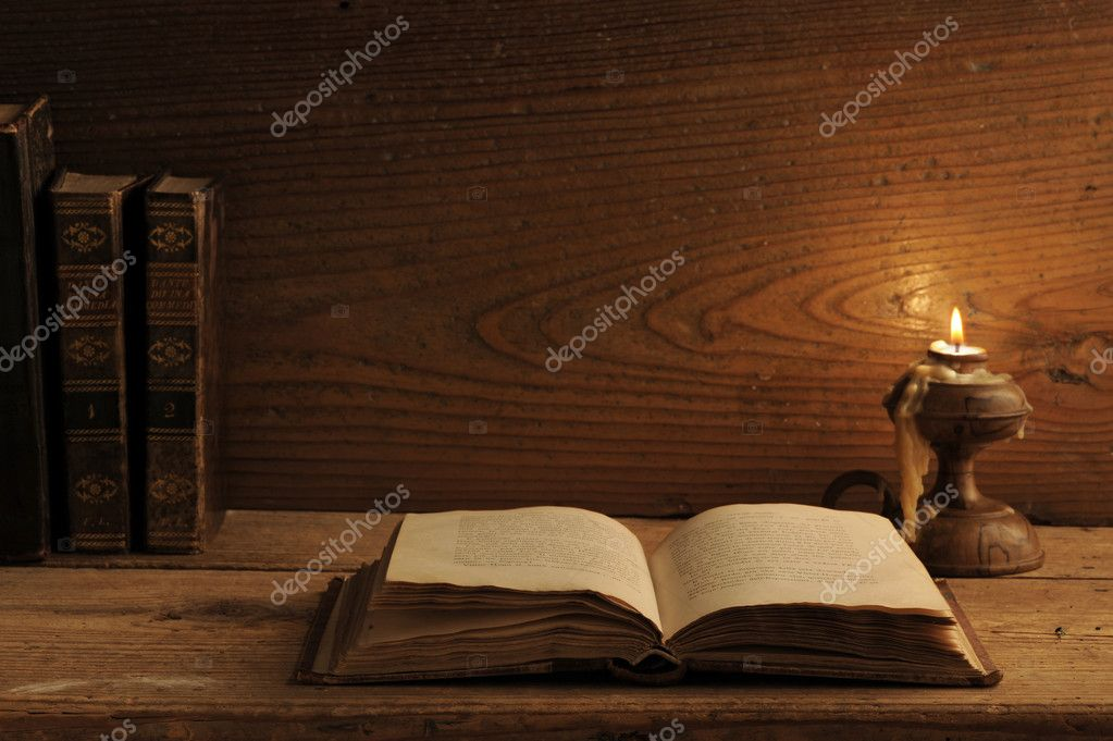 Old book on a wooden table by candlelight — Stock Photo #7717192
