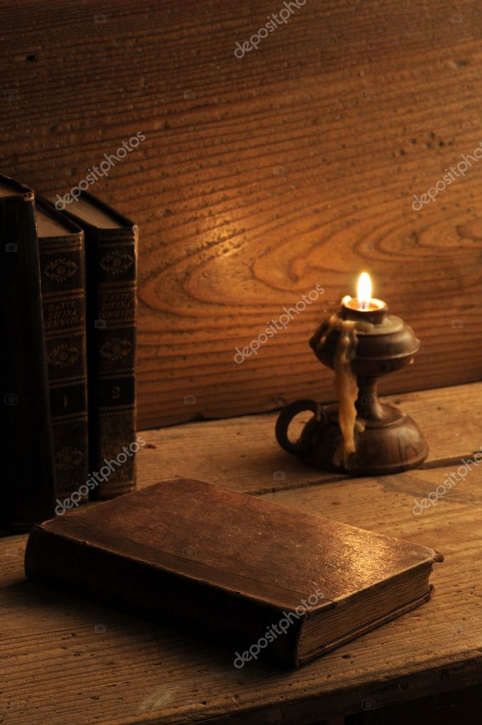 Old book on a wooden table by candlelight — Stock Photo #7717207