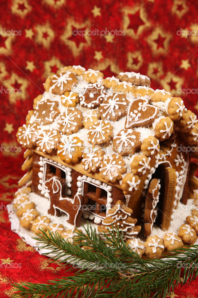 Christmas gingerbread house and spruce twig on red Christmas background — Stock Photo #7413907