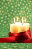 Candles with ribbon on Christmas background — Stock Photo