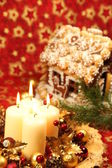 Christmas decoration with candles and gingerbread house — Stock Photo