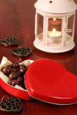 Heart shaped box with chocolate and lantern — Stock Photo