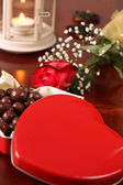 Heart shaped box with chocolate, rose and lantern — Stockfoto