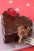 Heart shaped chocolate cake with a bite — Stock Photo