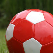Red soccer ball on grass — Stock Photo