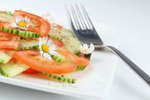 Vegetable salad with daisies — Stock Photo