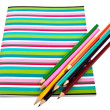 Exercise book with colorful pencils — Stock Photo