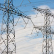 Two electricity pylons against a blue cloudsky — Stock Photo