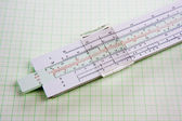 Old used slide rule on squared paper — Stock Photo
